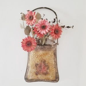 Wall pocket with floral arrangement.
